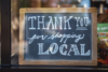 "A sign in a window that reads: ""Thank you for shopping local"""